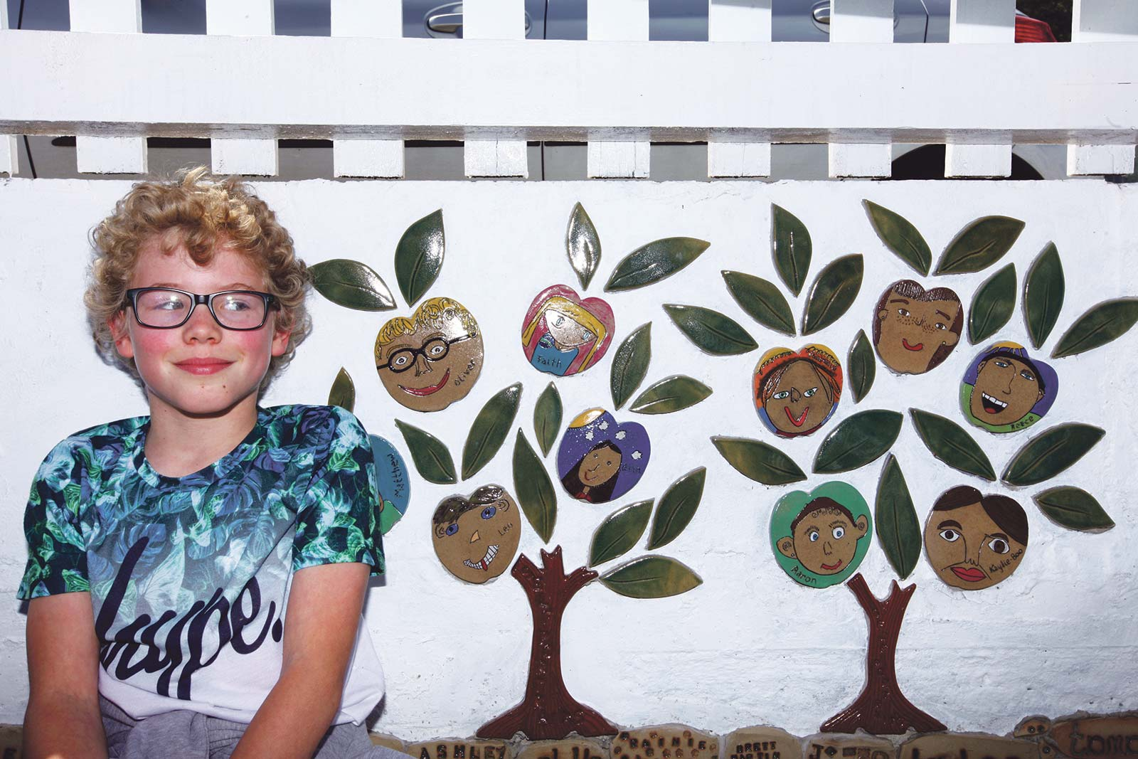 New artwork tiles at Gunnislake station - one of the young artists poses with the tile beaering his portrait